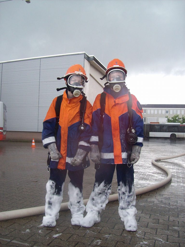 Zwei Jugendfeuerwehrleute tragen Atemschutz. Ihre Beine sind voller Löschschaum